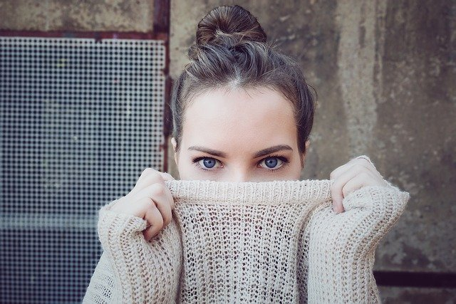 Lady with sweater covering face