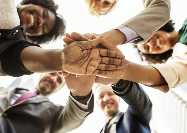 Diverse Group of People Gathered in a circle with their hands together in the middle