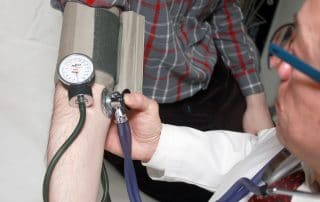 physician taking urgent care patient's blood pressure