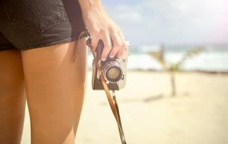 woman legs at beach with camera